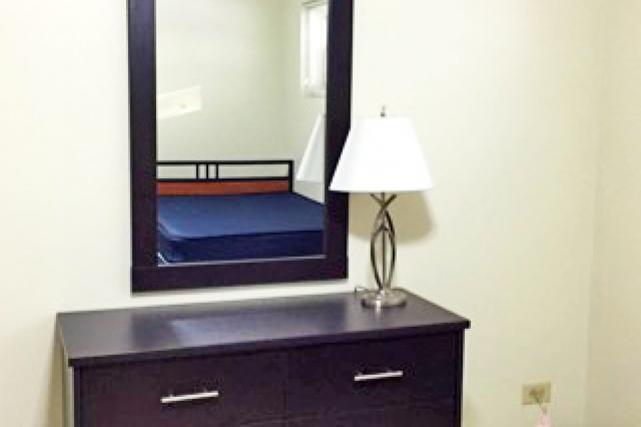 One-bedroom apartments are furnished with a mirror, two dressers, and lamps