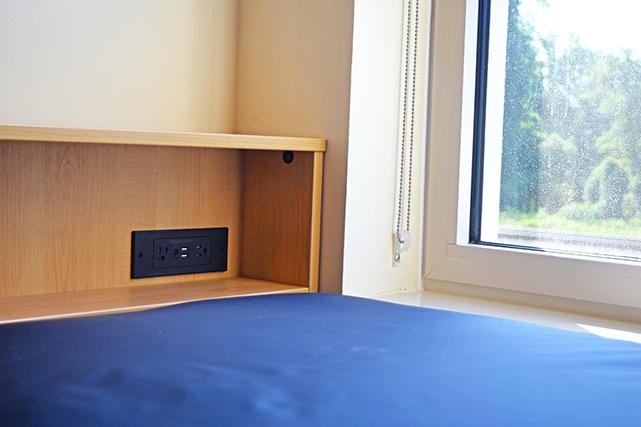 Headboards feature a built-in electrical outlet and shelf