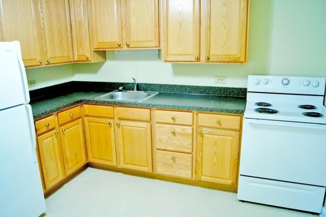 Kitchens include an electric range and refrigerator
